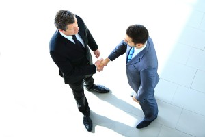 Top view of a two businessman shaking hands - Welcome to busines